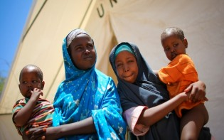 Two Somali girls hold their twin brothers outside a tented hospital ward at a free Outpatient's Department medical clinic, at the headquarters of the Burundian Contingent serving with the African Union Mission in Somalia (AMISOM), in Mogadishu. (UN Photo/Stuart Price)